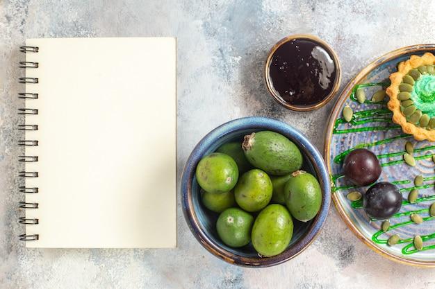 Top-down ontworpen fruitschaal met smakelijke zure rijpe pruimen rond wit leeg notitieboekje