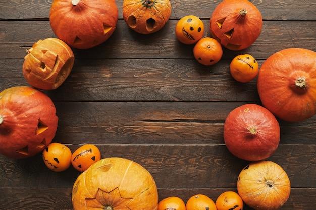 Top-down plat lag shot van rijpe oranje pompoenen gesneden en mandarijnen met gezichten getekend voor halloween liggend op bruin houten tafel in cirkel, kopie ruimte