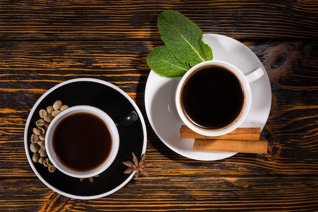 Top-down uitzicht op porties van koffie en thee in kopjes met bonen, kruiden en bladeren in schotel over donkere gekleurd houten tafel achtergrond