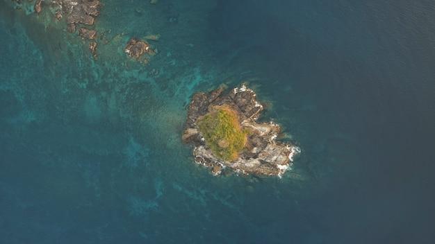 Top-down van rotseiland met groene piekantenne. oceaangolven crashen op kliffen. niemand tropische natuur