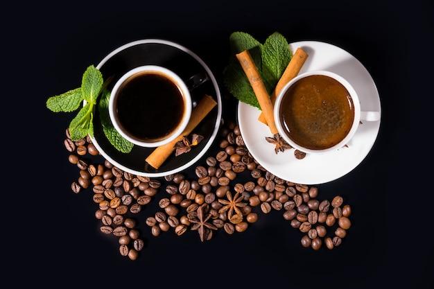 Top-down weergave van thee en koffie, omringd door bonen met kruiden op schoteltjes op zwarte achtergrond