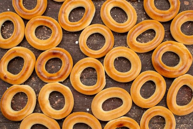 Top gesloten weergave zoete ronde crackers gedroogde en smakelijke snacks op bruin, koekjeskoekje drinken ontbijt