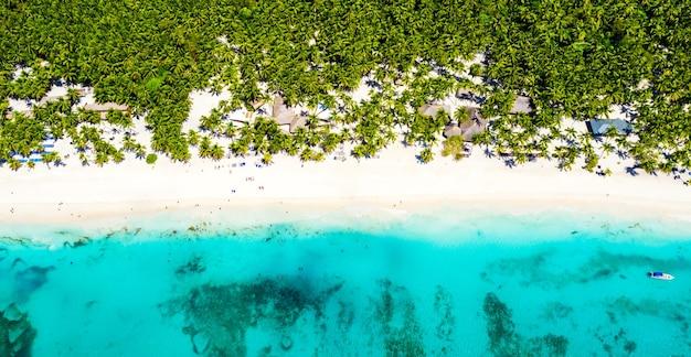 Top luchtfoto drone uitzicht op prachtig strand met turquoise zeewater, boten en palmbomen. saona-eiland, dominicaanse republiek. paradijs tropisch eiland natuur achtergrond.