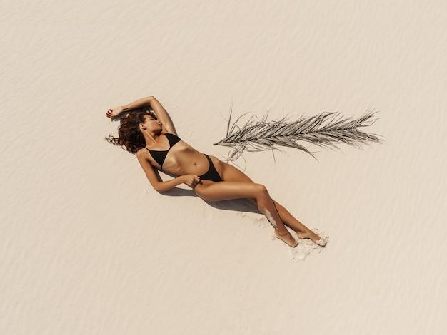 Top luchtfoto drone weergave van vrouw in badpak bikini ontspannen en zonnebaden op het strand