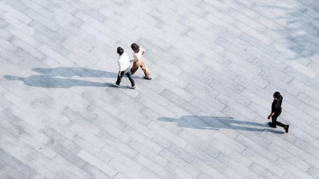Top luchtfoto sociale familie en vrienden mensen lopen door over voetgangers in open ruimte landschap.