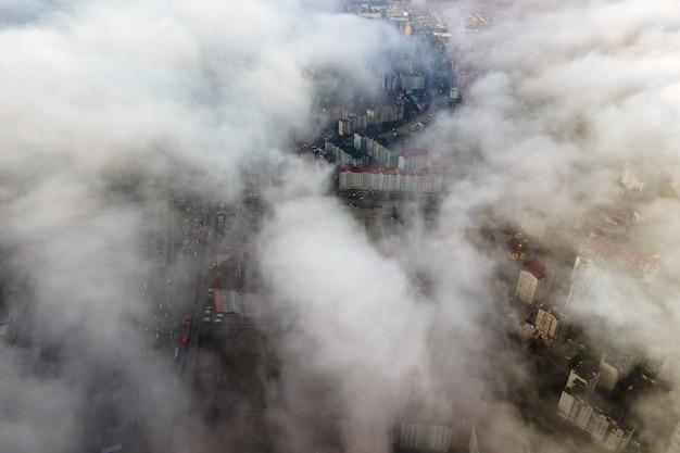 Top luchtfoto van pluizige witte wolken boven moderne stad met hoge gebouwen.