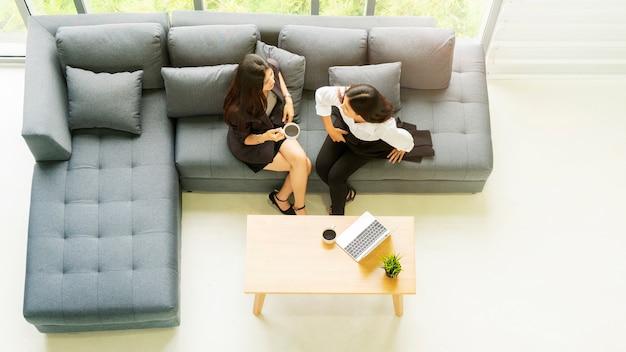 Top luchtfoto zakelijke vrouw praten en zitten op grijze bank bank met zwarte koffie drinken.