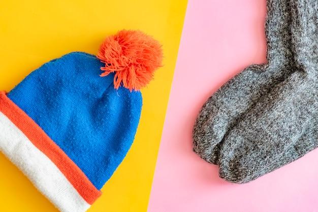 Top plat leggen van winterreisset met wollen hoed en creatieve sokken op roze en gele achtergrond f
