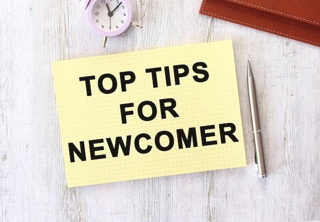 Top tips voor nieuwkomer tekst geschreven in een notitieboekje dat op een houten werktafel ligt