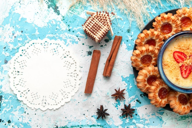 Top uitzicht heerlijke suikerkoekjes met aardbeiendessert op het blauwe bureau koekjeskoekje suiker zoete cake dessertkleur