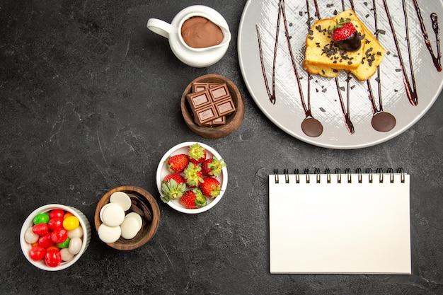 Top uitzicht van verre cake met aardbeien plaat van cake met aardbeien naast de kommen van snoep chocolade aardbeien en chocolade crème en wit notitieboekje