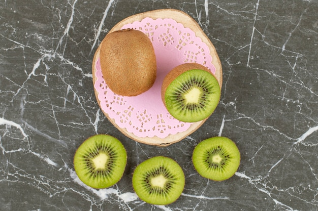 Top-up foto van hele en gesneden kiwi's op een houten bord over zwart.