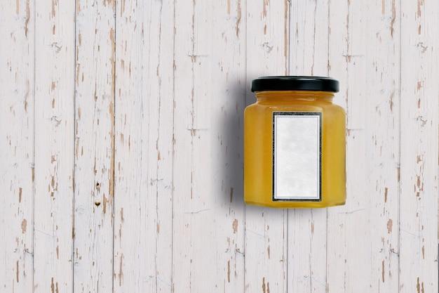 Top-up weergave oranje jampot geïsoleerd op een witte houten achtergrond. geschikt voor uw ontwerpproject.