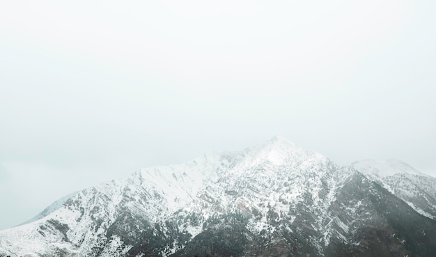 Top van een besneeuwde berg met mist