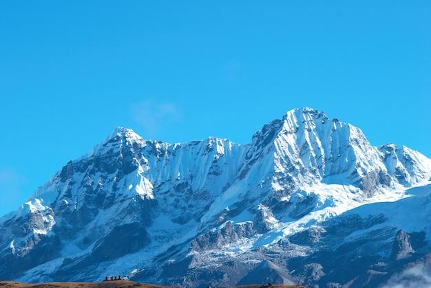 Top van hoge bergen, vallende sneeuw. kangchenjunga, india.