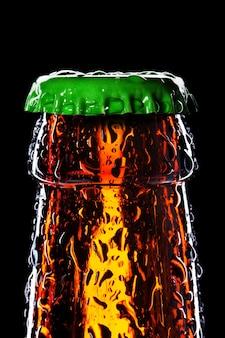 Top van natte bierfles geïsoleerd op zwart