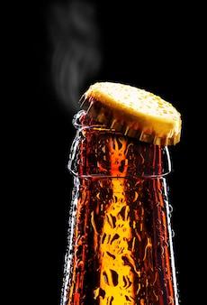Top van open natte bierfles geïsoleerd op zwart
