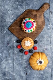 Top verre uitzicht heerlijke cake met slagroom en snoep, samen met bessen cookie cakes op licht