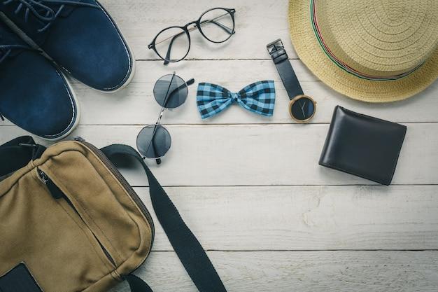 Top view accessoires om te reizen met man kleding concept. strikje, portemonnee op houten background.watch, zonnebril, tas, hoed en schoenen op houten tafel.