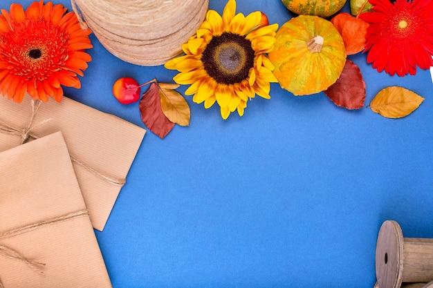 Top viewhandcraft geschenkdoos, gele en oranje bloemen en pompoenen op blauwe achtergrond.