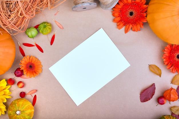 Top viewhandcraft geschenkdoos, gele en oranje bloemen en pompoenen op roze achtergrond.