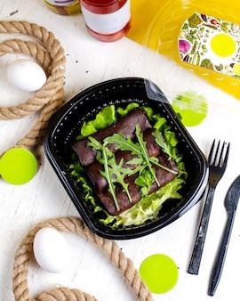 Top zwarte pannenkoeken met urugula in bezorgdoos op tafel