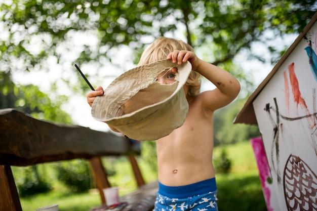 Topless kleine blonde jongen met hoed schilderen buiten in de zomer, spelen.