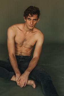Topless knappe jonge russische mannelijke model zittend op de groene vloer