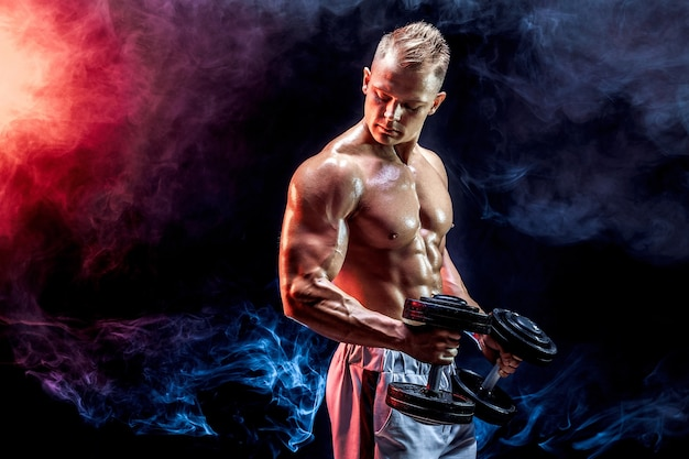Topless man biceps uitoefenen met halters poseren in studio vol