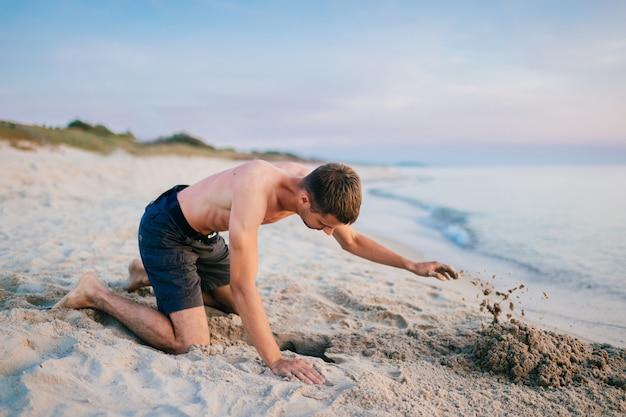 Topless man in korte broek staande op de knieën en graven pit door handen op het strand buiten de zee in de zomeravond.