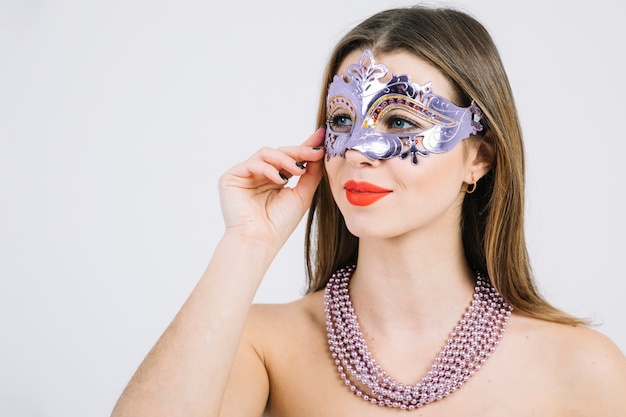 Topless vrouw in carnaval-masker met parelshalsband op witte achtergrond