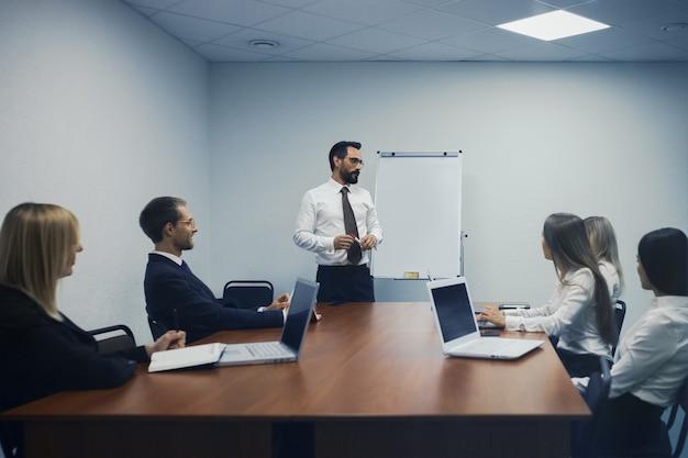 Topmanagerbijeenkomst in modern kantoor. spreker man staat in de buurt van whiteboard met discussie