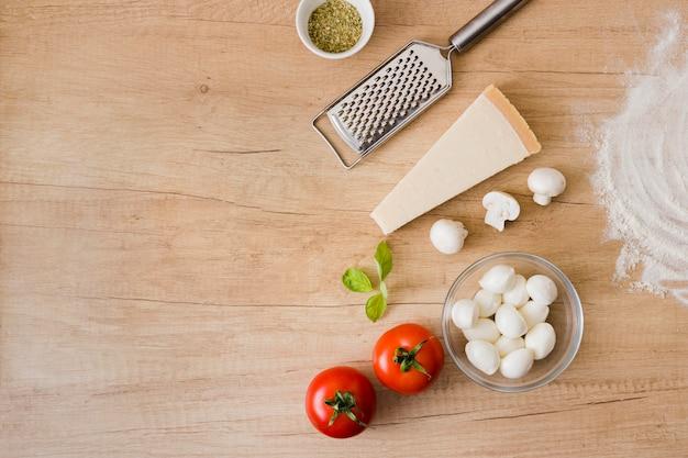 Topping-ingrediënten voor pizza met metalen rasp op houten achtergrond