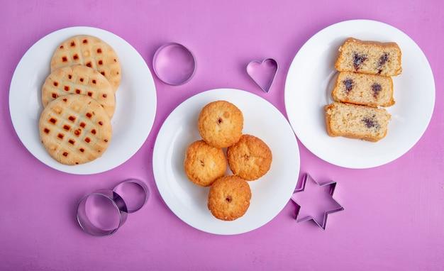 Topv uitzicht op koekjes en muffins op platen en cookie cutters op paarse achtergrond