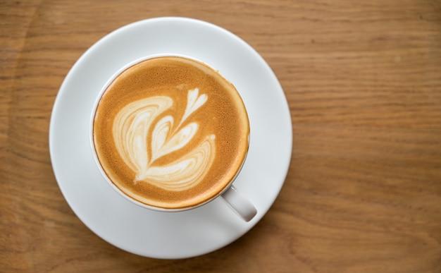 Topview shot van koffie latte hart textuur op houten vloer.
