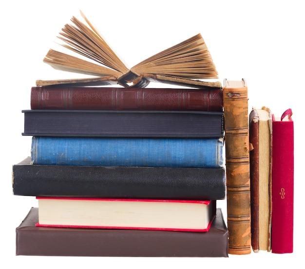 Toren van boeken met open boek bovenop geïsoleerd op wit
