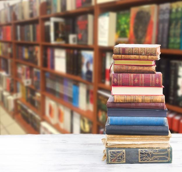 Toren van boeken op wit houten bureaublad in boekhandel