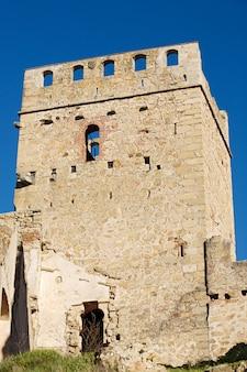 Toren van een kasteel in ruïnes op een blauwe hemel