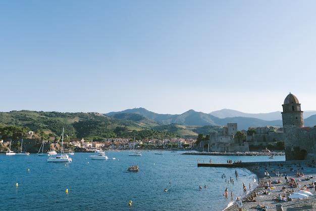 Toren van het kasteel in een middeleeuwse haven met boten en mensen op het strand. reis concept