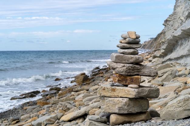Toren van kiezelstenen tegen de zee.