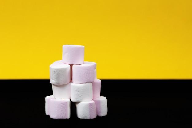 Toren van marshmallow snoepjes op een gele en zwarte achtergrond. detailopname