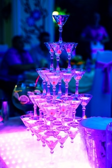 Toren van martini-glazen in restaurant met ultraviolette verlichting