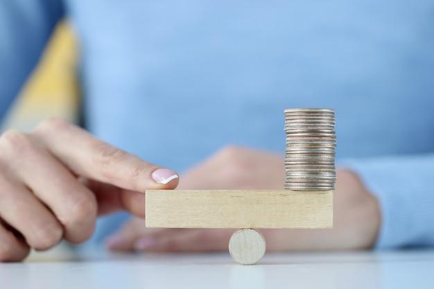 Toren van munten op houten blok en vinger aan de andere kant. investeringen en handelsconcept