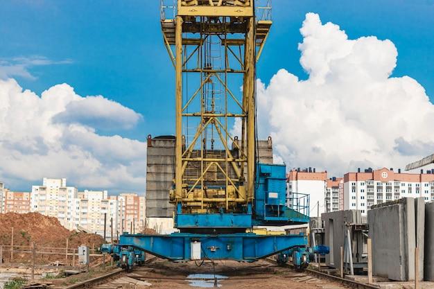 Torenkraan op rails close-up op de bouwplaats tegen de achtergrond van de bewolkte hemel. close-up van zware bouwmachines voor het heffen en verplaatsen van lasten. bouw kraan.