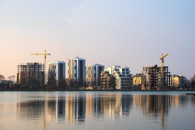 Torenkranen en hoge residentiële flatgebouwen in aanbouw aan de oever van het meer.