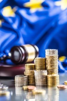 Torens met euromunten vlag van de europese unie en justitie hamer op de achtergrond.