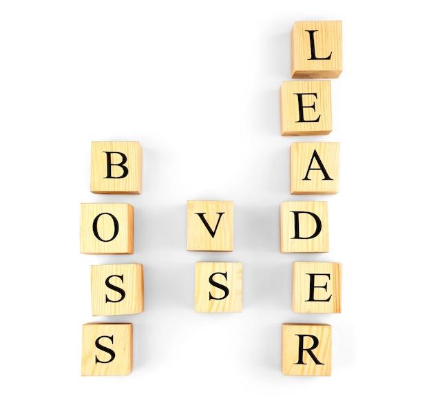 Torens van houten kubussen met tekst boss vs leader geïsoleerd op wit