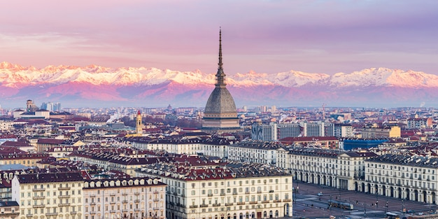 Torino skyline, stadsgezicht bij zonsopgang met details van de mole antonelliana torenhoog over de stad. toneel kleurrijk licht op de besneeuwde alpen op de achtergrond.