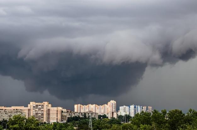 Tornado, onweer, trechterwolken boven de stad.