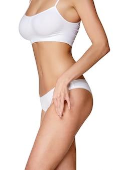 Torso van vrouw in het witte bikini zonnebaden